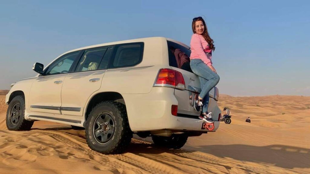 Tourist standing with the jeep at desert safari tour